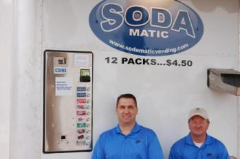 Melvin Eaker (left) and Dan Cooper stand in front of the Sodamatic Vending Machine.